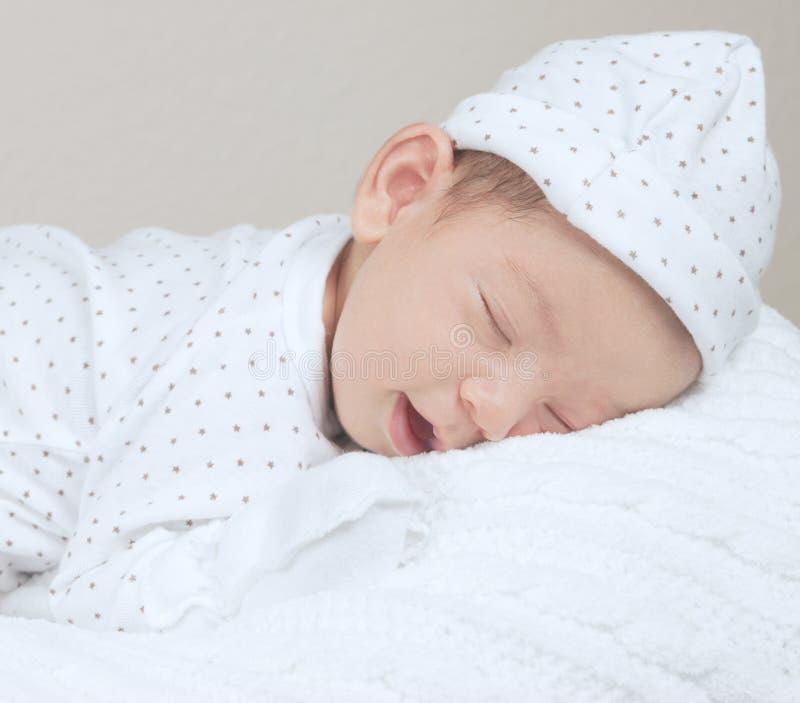 新出生的微笑的和睡觉的婴孩画象  库存图片