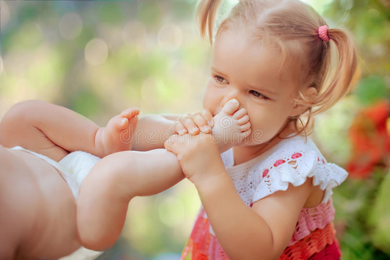 新出生的汤的姐妹佩带的crochetting的礼服亲吻的脚 免版税库存图片