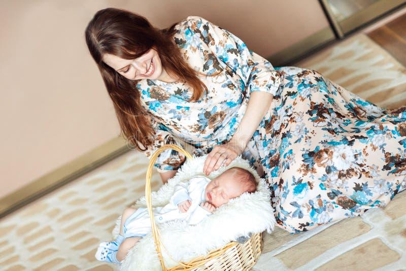 新出生的男婴在篮子的,抚摸新出生的妈妈 库存照片