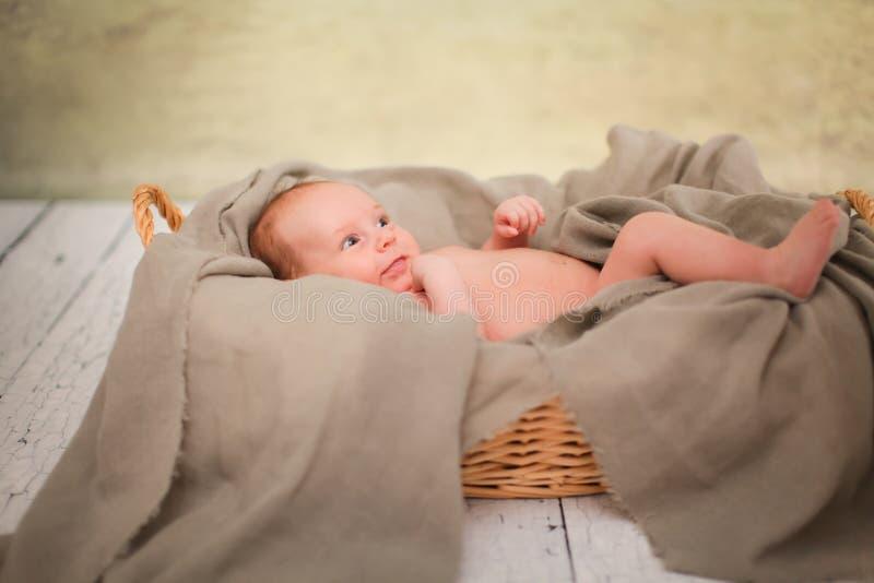 新出生的赤裸婴孩在柳条筐在 在白色木背景的篮子 新出生的照片写真 库存照片