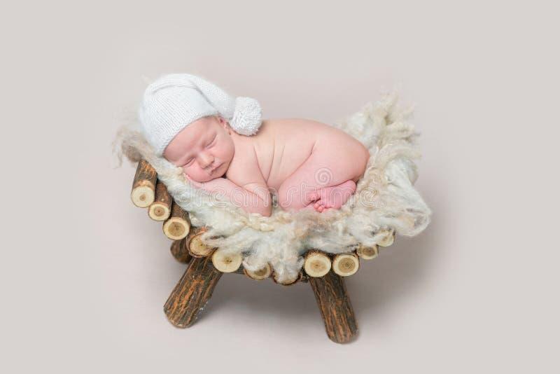 新出生的婴孩在一个木小儿床睡觉 图库摄影