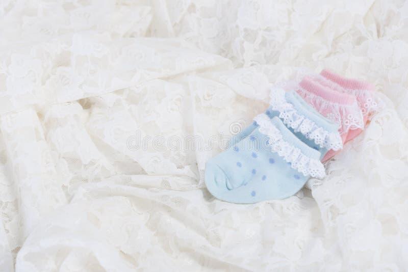 新出生的婴孩的婴孩袜子婚礼的系带背景 免版税库存图片