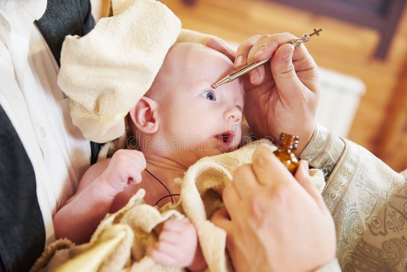新出生的婴孩的Chrismation圣礼在洗礼仪式期间的 免版税库存图片