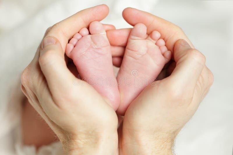 新出生的婴孩,在父亲手的脚 免版税图库摄影
