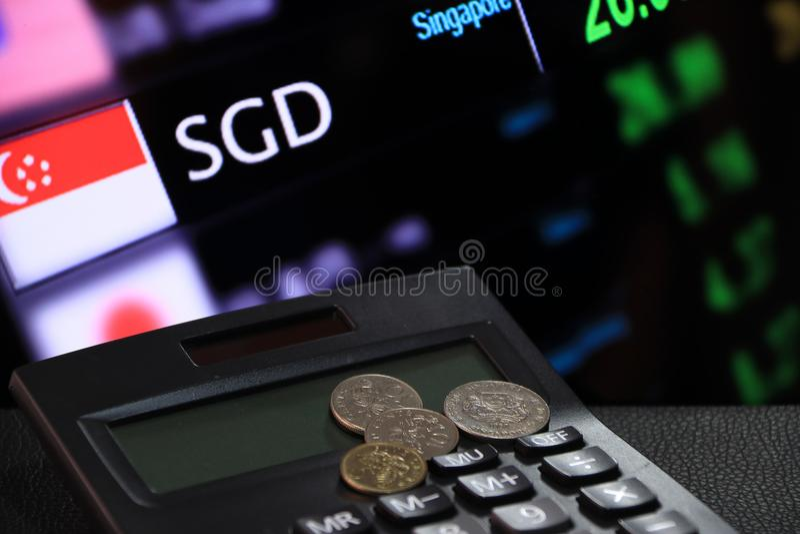 新加坡分铸造在黑计算器的SGD有汇兑金钱背景数字式板的  免版税图库摄影