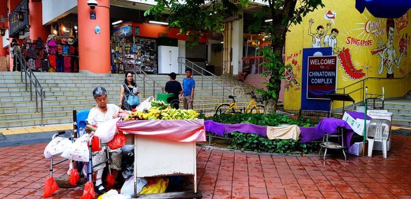 新加坡,新加坡2018年6月29日:卖在街道食物市场上的老妇人果子与被弄脏的人民和许多商店背景 库存照片