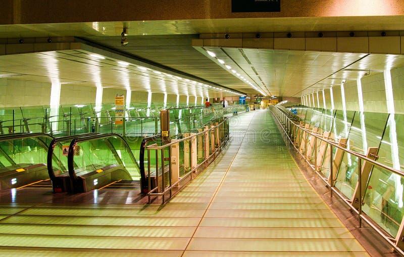 新加坡,新加坡- 3月24 2008年:在长的走廊的看法在有移动的台阶的国际机场里面对天空火车站 库存图片