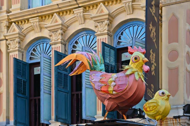 新加坡,鸡装饰和老殖民地大厦与蓝色窗口在街道上在中国镇区 库存图片