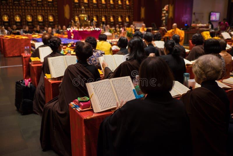 新加坡- 2016年5月2日:祈祷在菩萨牙遗物寺庙和博物馆的修士和佛教徒 道士佛教寺庙安置a 免版税库存照片