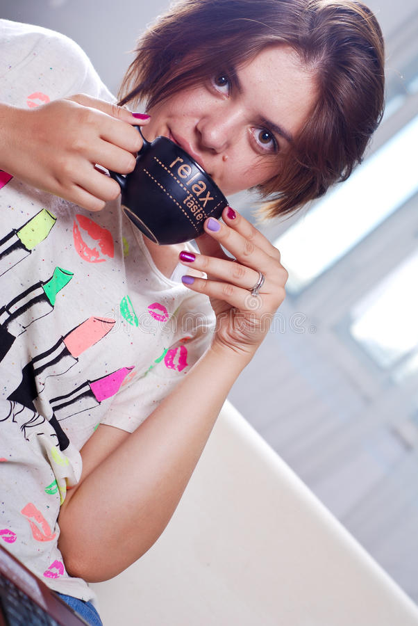 新可爱的妇女喝咖啡 免版税库存照片