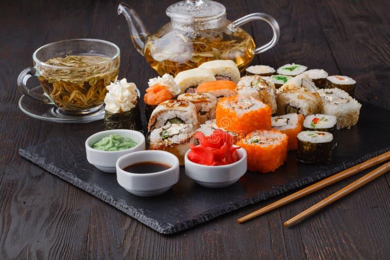 新和可口maki和nigiri寿司卷和绿茶玻璃 免版税图库摄影
