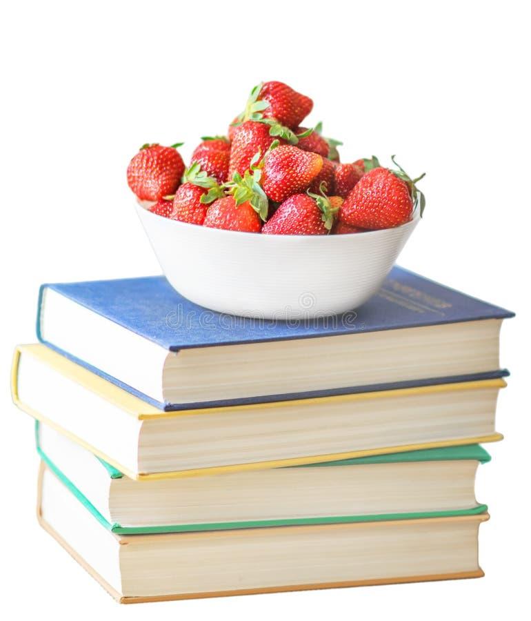 新在一个白色在白色背景隔绝的盖帽在堆或堆书或classbooks的夏天红色草莓 概念  免版税库存图片