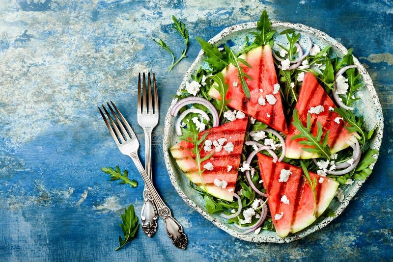 新夏天烤了西瓜沙拉用希腊白软干酪,芝麻菜,在蓝色背景的葱 免版税库存图片