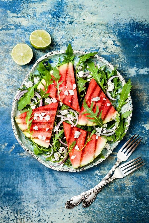 新夏天烤了西瓜沙拉用希腊白软干酪,芝麻菜,在蓝色背景的葱 库存照片