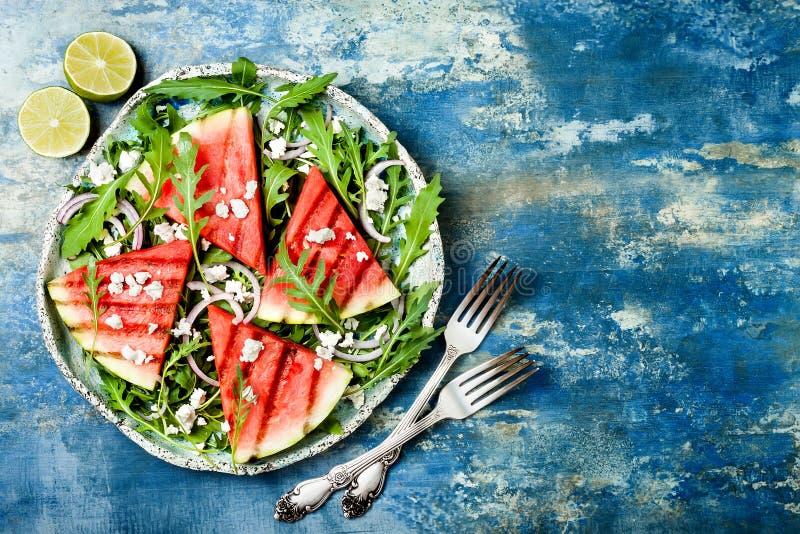 新夏天烤了西瓜沙拉用希腊白软干酪,芝麻菜,在蓝色背景的葱 库存图片