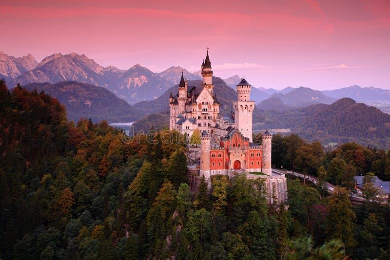 新天鹅堡城堡的美好的晚上视图,与在日落以后的秋天颜色,巴法力亚阿尔卑斯,巴伐利亚,德国 库存照片