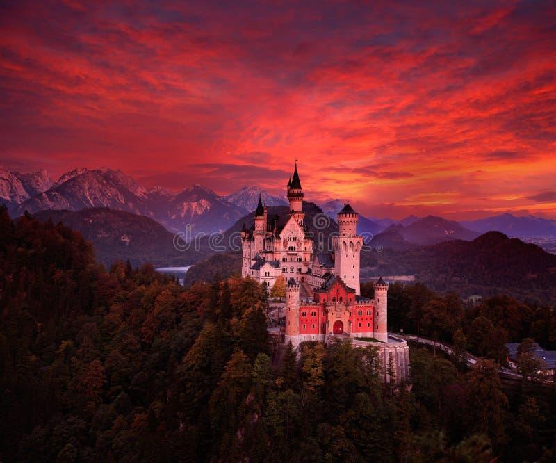 新天鹅堡童话城堡的美好的清早视图,与秋天颜色的血淋淋的黑暗的天空在sunr期间的树 免版税库存照片