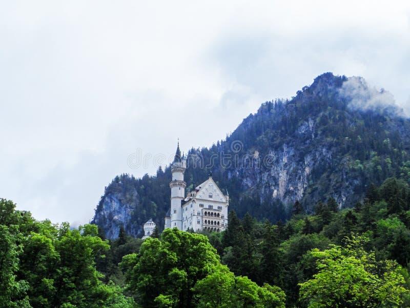 新天鹅堡,德国城堡  从湖的看法有树、云彩和山的在背景 免版税库存图片