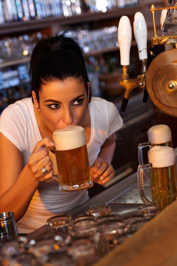 新女性酒吧招待品尝桶装啤酒 图库摄影