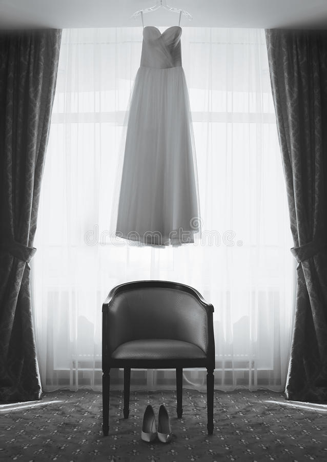 新娘、婚礼礼服和鞋子,椅子的室 免版税库存照片