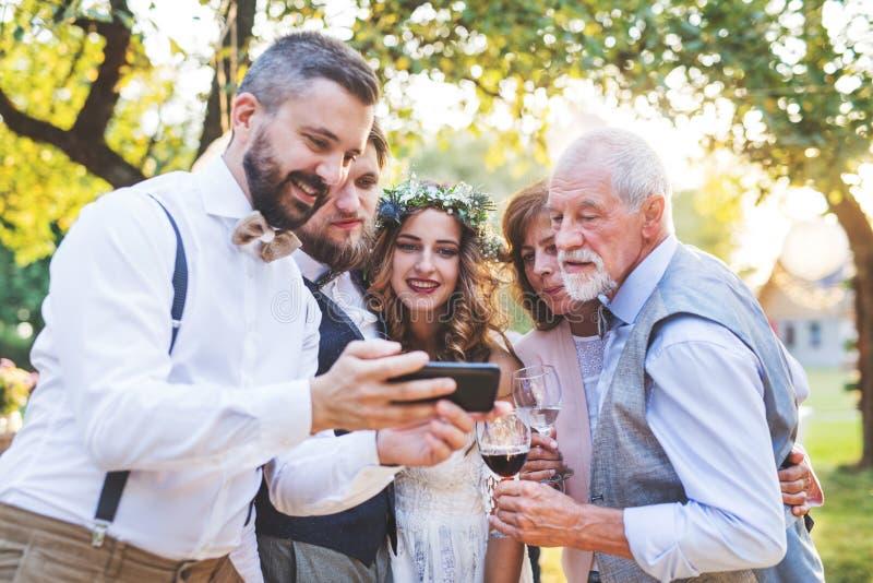新娘、新郎和客人有采取selfie的智能手机的外面在结婚宴会 免版税库存照片