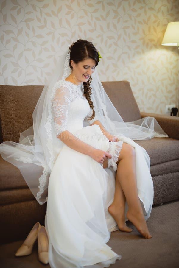 新娘佩带在腿的一条婚礼袜带 图库摄影