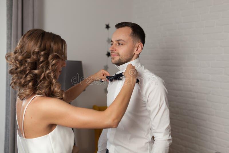新娘修理在新郎s脖子的蝶形领结 免版税库存照片