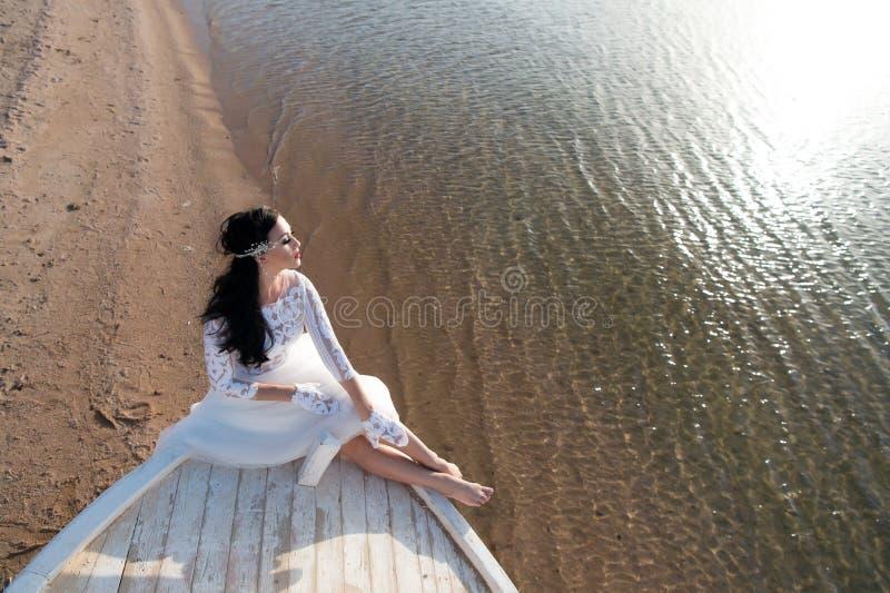 新娘可爱的白色婚礼礼服晴天坐小船或船 蜜月海海滩 事为婚姻考虑 免版税库存照片