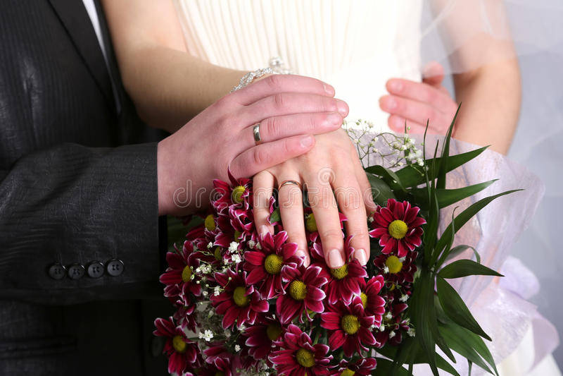 新娘和女傧相婚礼花束的手 免版税库存照片