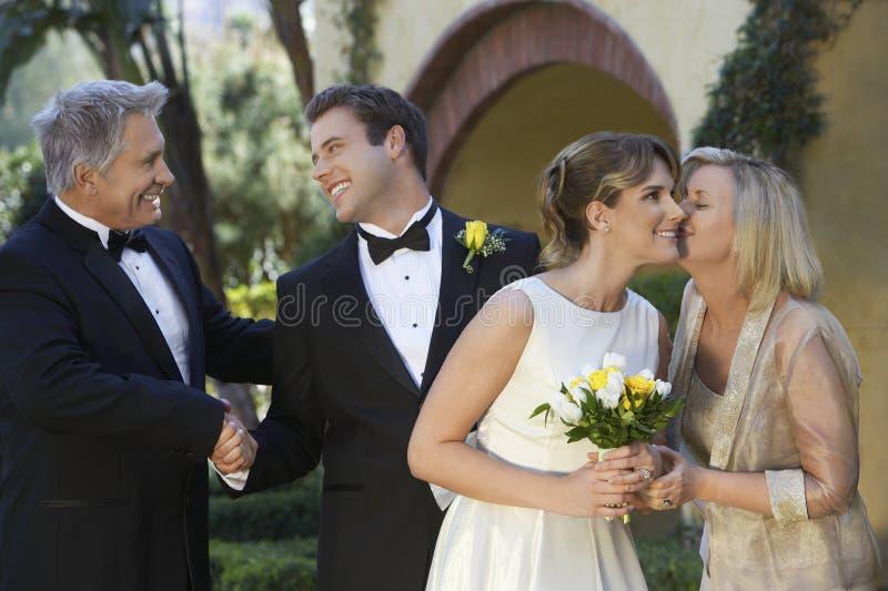 新娘和新郎与父母 免版税库存照片