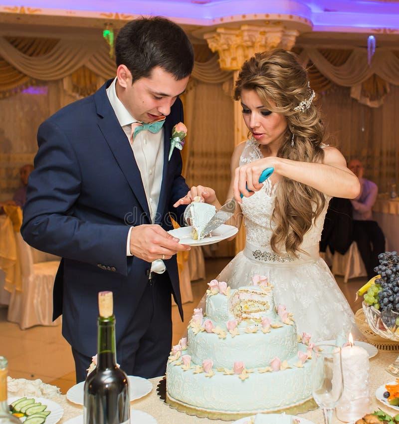 新娘和新郎切他们的婚宴喜饼 免版税库存照片