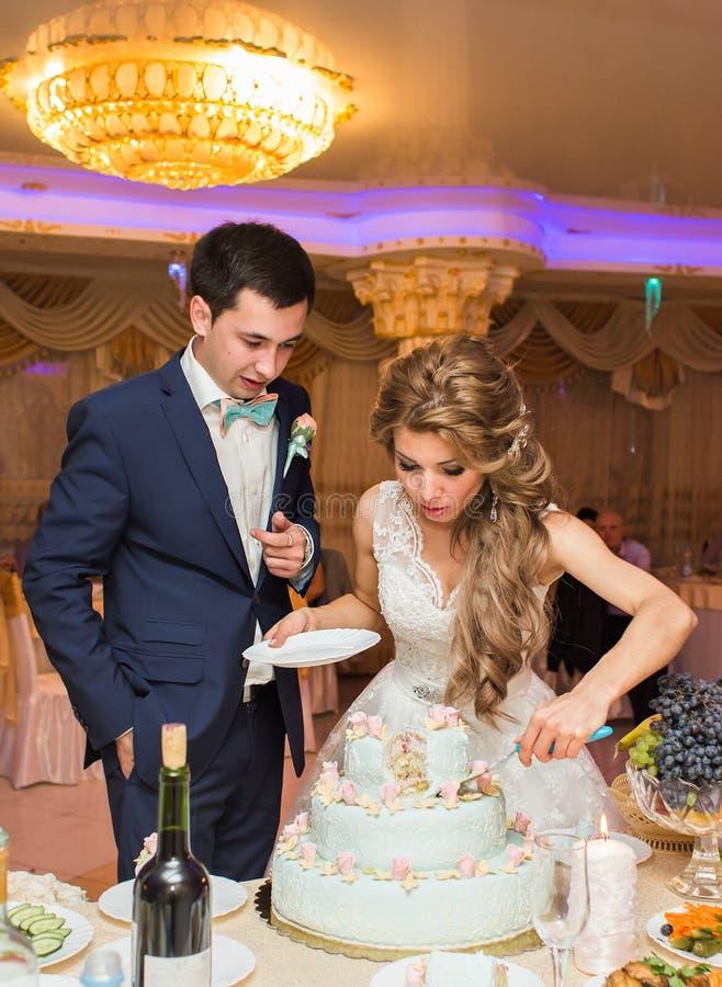 新娘和新郎切他们的婚宴喜饼 免版税图库摄影