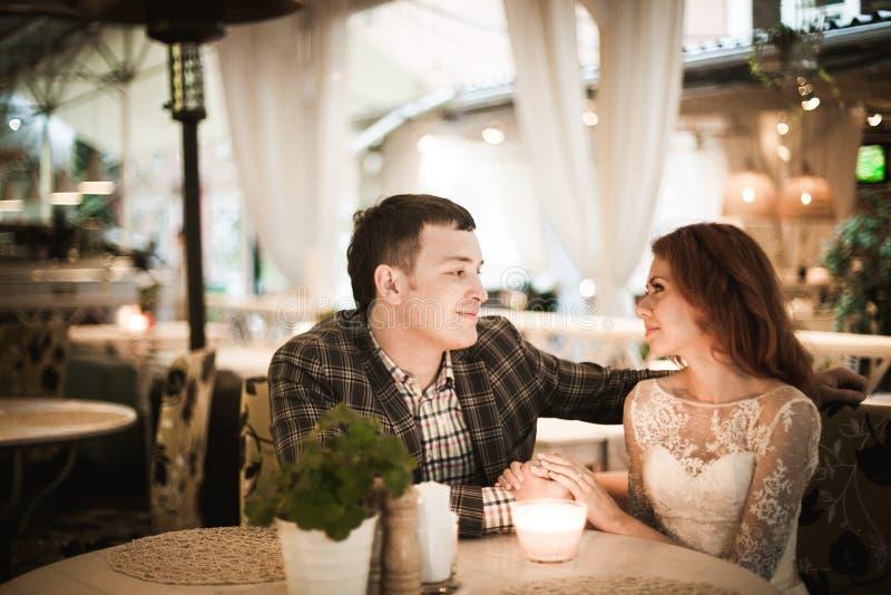 新娘和新郎吃浪漫晚餐在街道咖啡馆 图库摄影