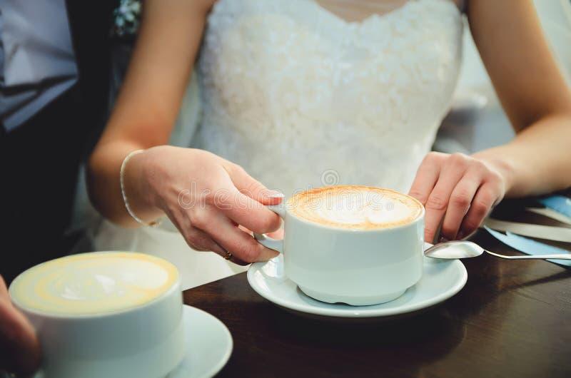 新娘和新郎在他们的婚礼那天,在咖啡馆的饮料咖啡 库存图片