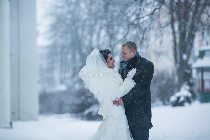 新娘和新郎在冬天城市的背景 免版税库存照片