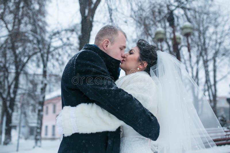 新娘和新郎在冬天城市的背景 库存图片