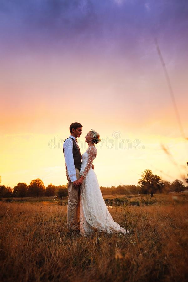 新娘和新郎在婚礼以后支持湖, 新婚佳偶微笑着 在温暖设色的现出轮廓的照片 免版税库存图片