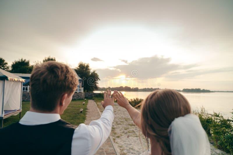 新娘和新郎在婚礼礼服在自然本底 新婚佳偶沿河岸走在日落 库存照片