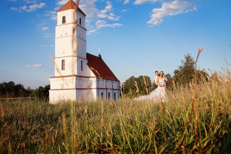 新娘和新郎在教会附近 免版税库存照片