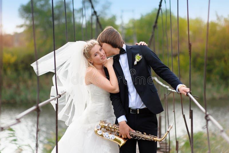 新娘和新郎在桥梁站立 免版税库存图片