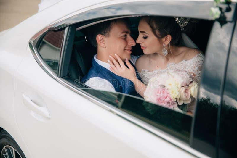 新娘和新郎在汽车的后座在她的手上坐,女孩拿着花花束  免版税库存图片