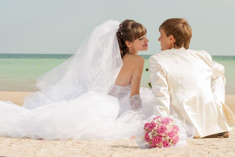 年轻新娘和新郎在海滩 库存图片