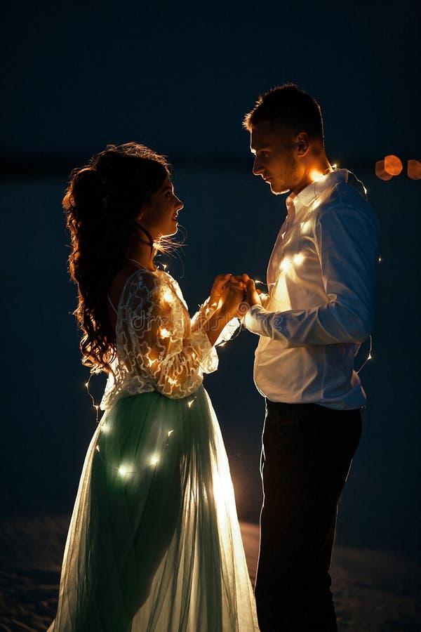 新娘和新郎在电灯泡旁边诗歌选站立并且握手在晚上 特写镜头 免版税图库摄影