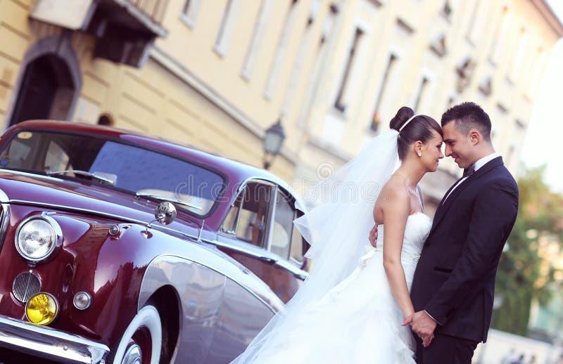 新娘和新郎在葡萄酒汽车附近 免版税库存照片