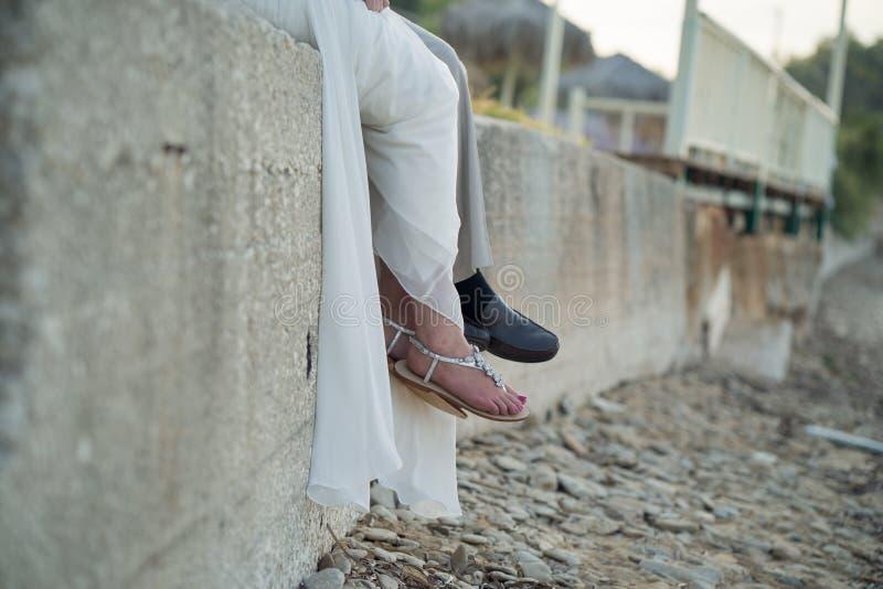 新娘和新郎坐岩石墙壁由海滩 库存照片