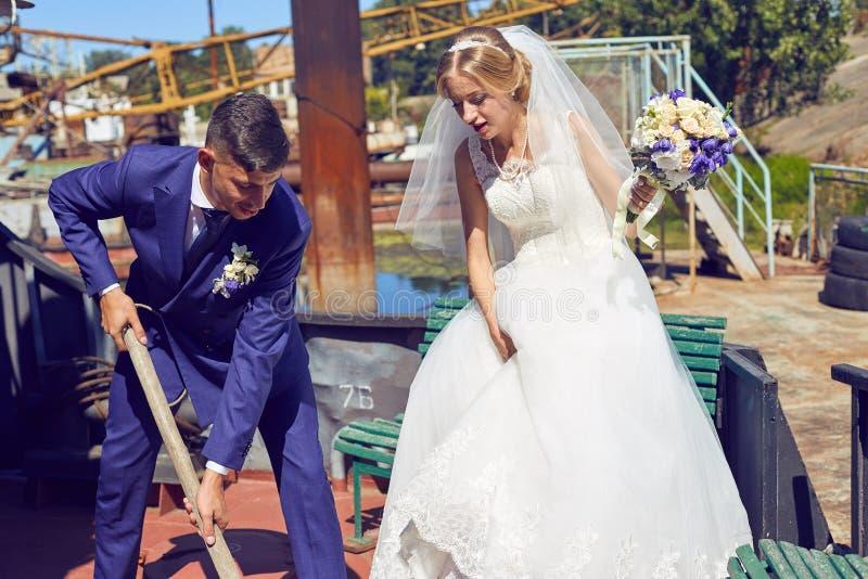 新娘和新郎婚礼之日获得乐趣在口岸 免版税库存照片