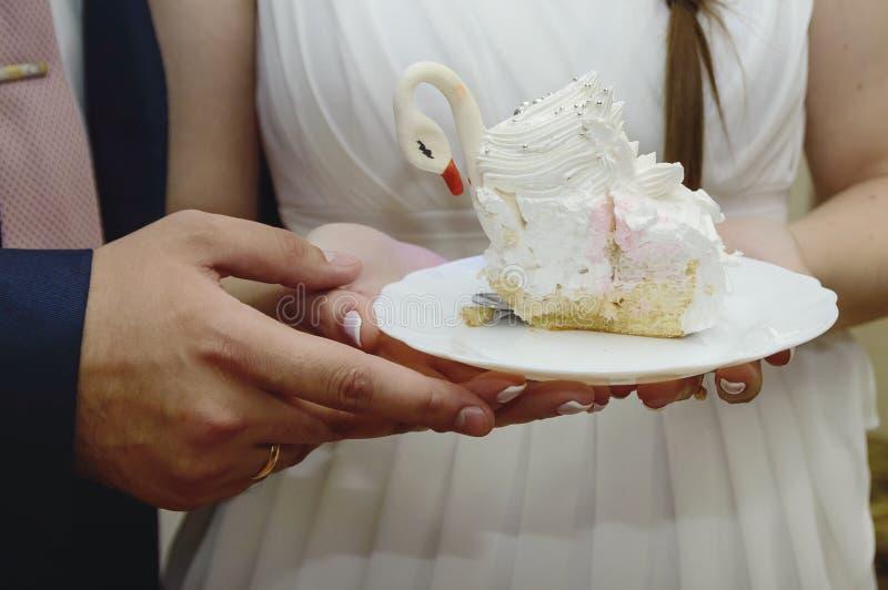 新娘和新郎拿着婚宴喜饼,特写镜头片断  免版税库存图片