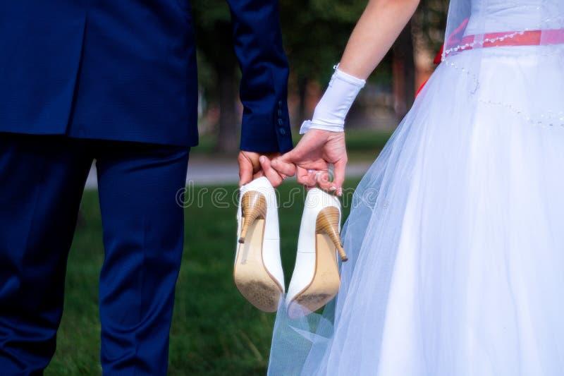 新娘和新郎拿着新娘的鞋子在他们自己之间的和握有他们的小指的手 详细婚礼 免版税库存图片