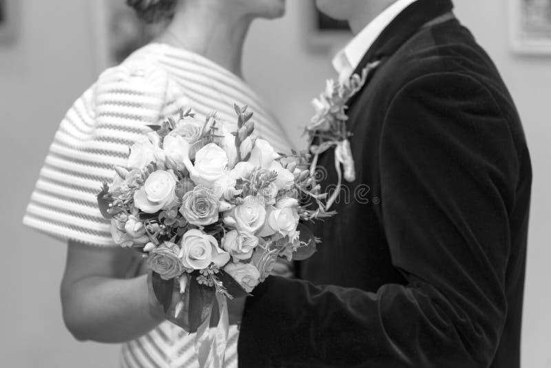 新娘和新郎拿着玫瑰花束,特写镜头,黑白照片 库存照片