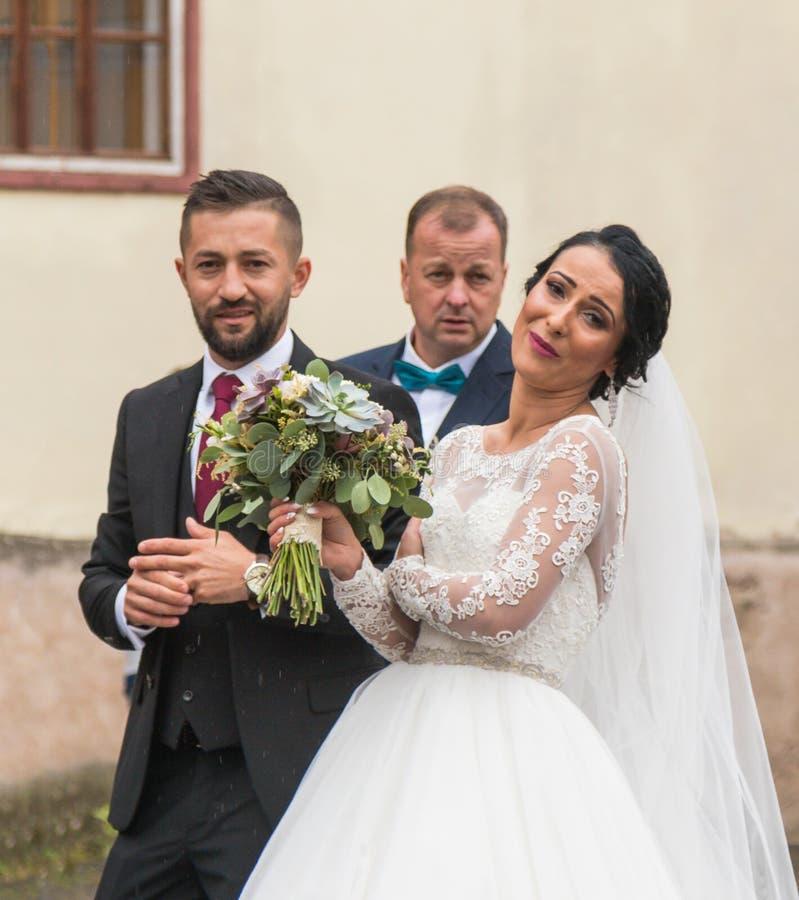 新娘和新郎是微笑和摆在为在教会前面的摄影师小正方形的 锡比乌市在罗马尼亚 免版税库存照片